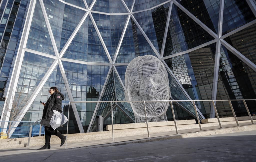 A pedestrian walks past The Bow building where Encana Corp. has it's company headquarters in Calgary on October 31, 2019. The brand Encana Corp. immediately brings to mind two things: energy and Canada. But Ovintiv, the name with which the oil and gas producer plans to re-christen itself once it moves its home base to the United States next year, offers no hint of what it does or where it's from. Branding experts say that's likely the point. THE CANADIAN PRESS/Jeff McIntosh.