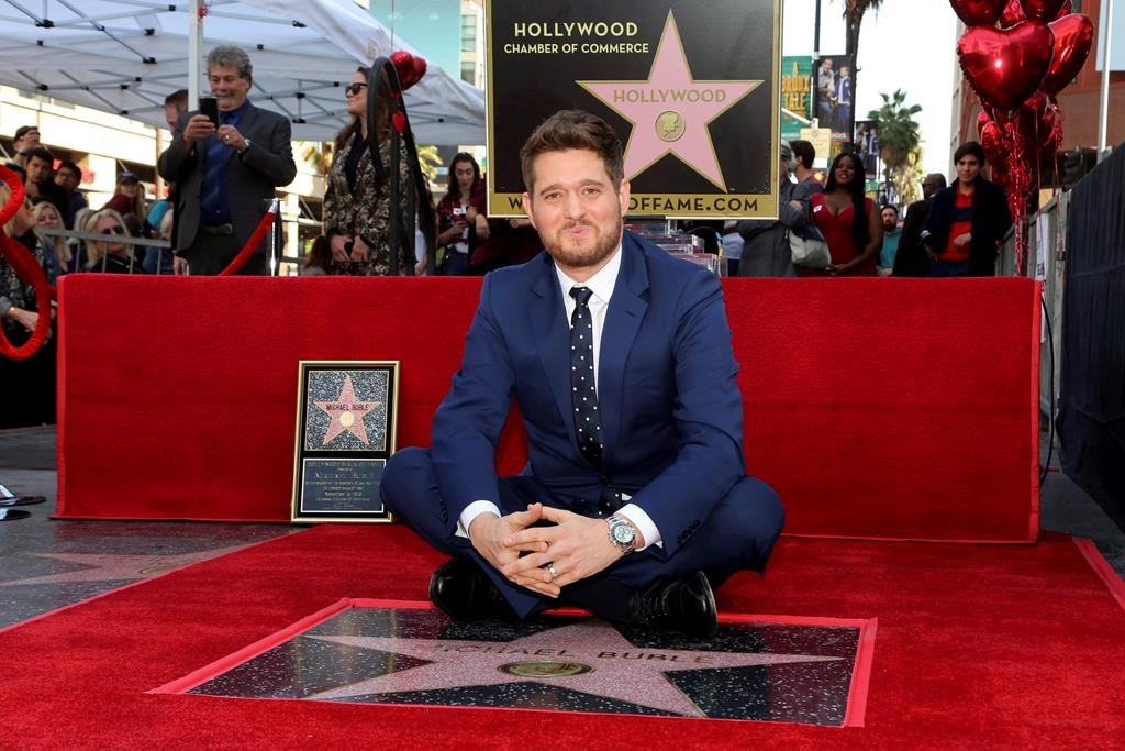 Michael Buble sits atop his star at a ceremony honouring him with a star on the Hollywood Walk of Fame in Los Angeles, Friday, Nov. 16, 2018.