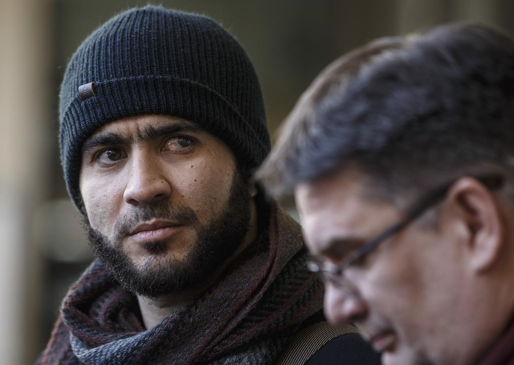 Former Guantanamo Bay prisoner Omar Khadr and his lawyer Nate Whitling speak with media outside the courthouse in Edmonton on February 26, 2019.