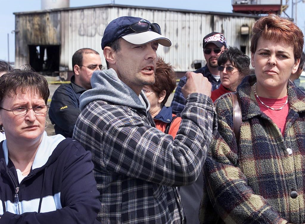 Angry out-of-work fish plant workers express their frustration outside their burned-out plant in Shippagan, N.B on Tuesday, May 6, 2003. Several boats and buildings were destroyed by fire on the weekend as fishermen protested cuts to the crab quota. A Moncton judge has dismissed a $40 million lawsuit against the RCMP and ordered the receivers of a Shippagan fish plant — destroyed in a riot in 2003 — to pay $210,000 in legal costs.