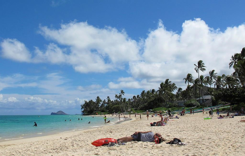 FILE - This Oct. 29, 2013 file photo shows people at Lanikai Beach, a popular neighborhood for vacation rentals, in Kailua, Hawaii. A judge has ruled that Hawaii tax authorities may subpoena Airbnb for records of its hosts as part of an investigation into whether operators of vacation rentals have been paying their taxes. Airbnb says it will hand over records of 1,000 Hawaii hosts who received the most revenue from 2016 through 2018. (AP Photo/Audrey McAvoy, File).