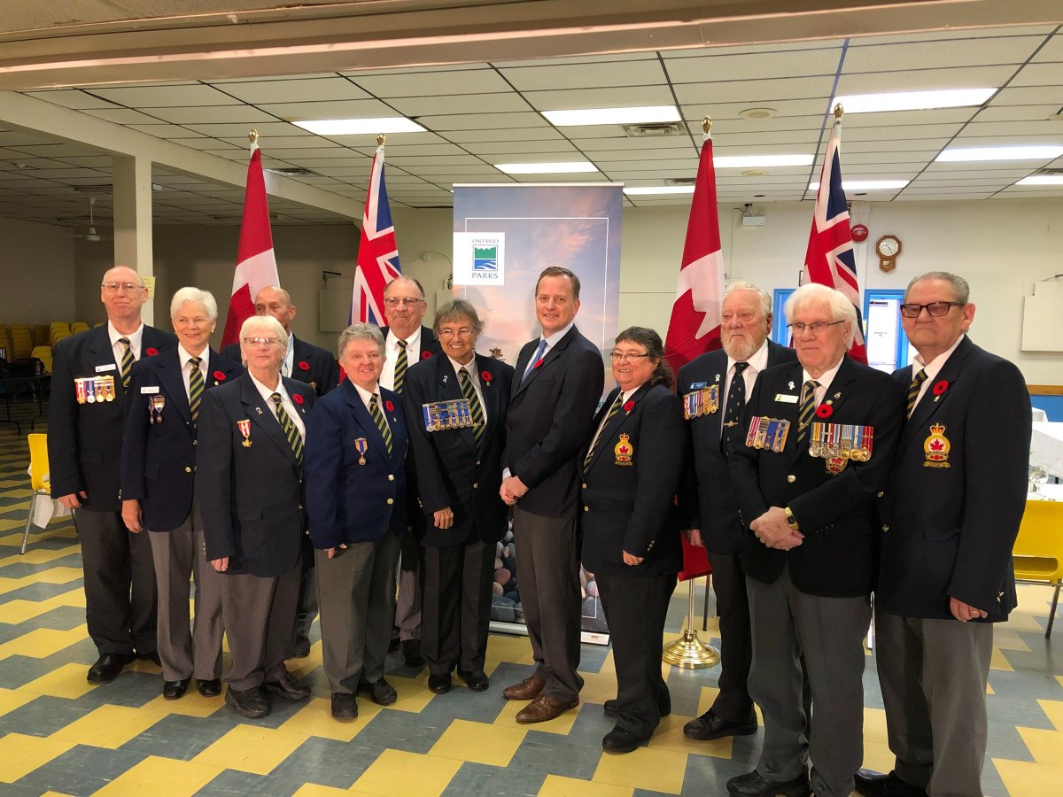 Environment Minister Jeff Yurek (middle) poses with a group of veterans and members from the Royal Canadian Legion in St. Thomas following Friday's announcement.