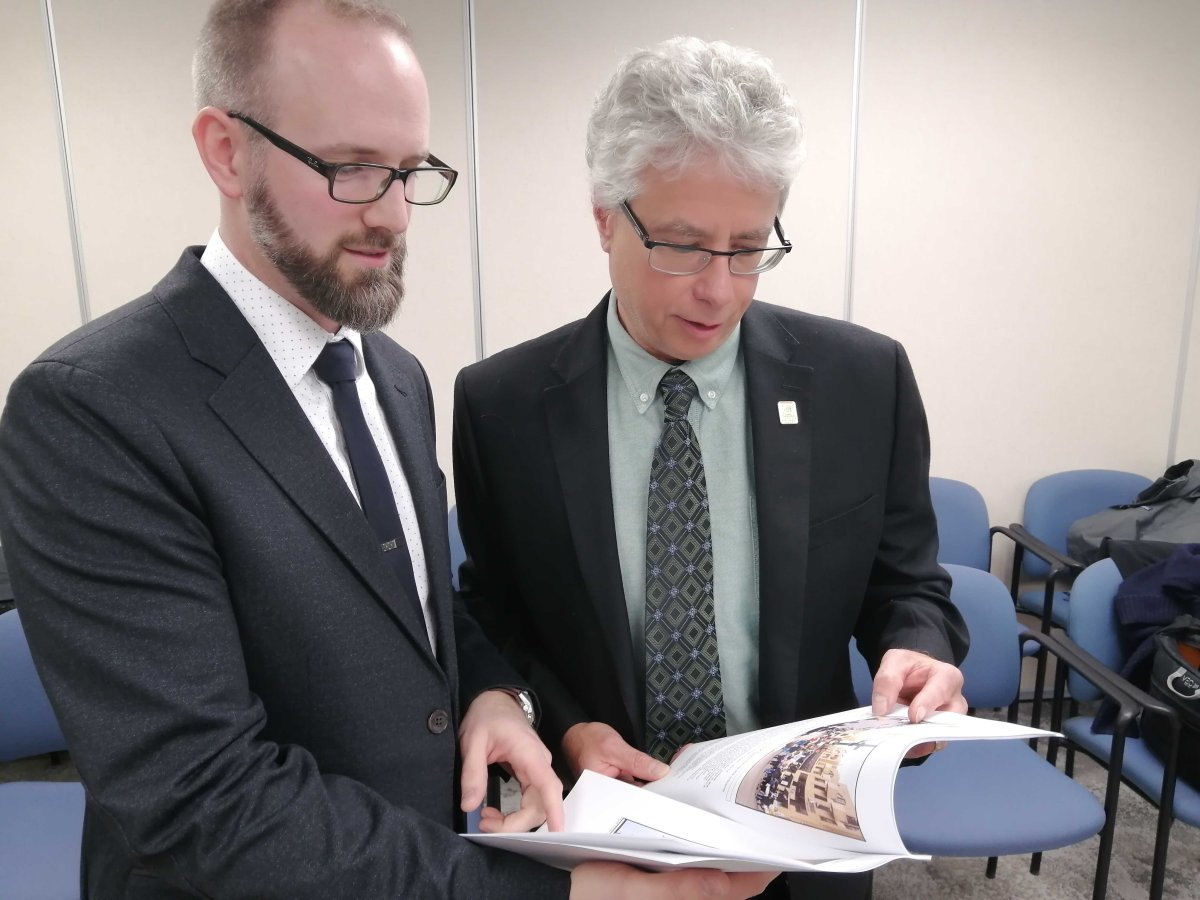 Sustainability and resiliency manager Mike Fabro (left) and environment, fleet, and solid waste director Jay Stanford (right) flip through a climate change emergency update report on Wed., Nov. 20, 2019.
