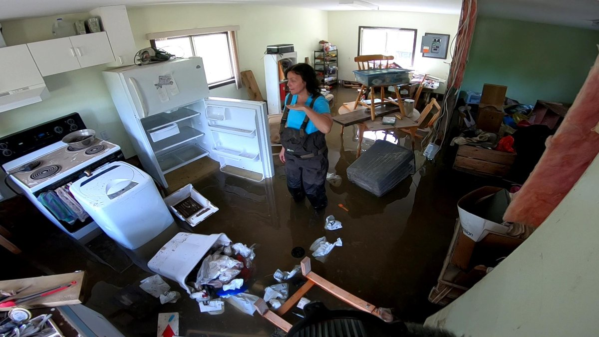 Jennifer Houghton stands in her flooded home indicating the high water mark with her hand in May 2018.