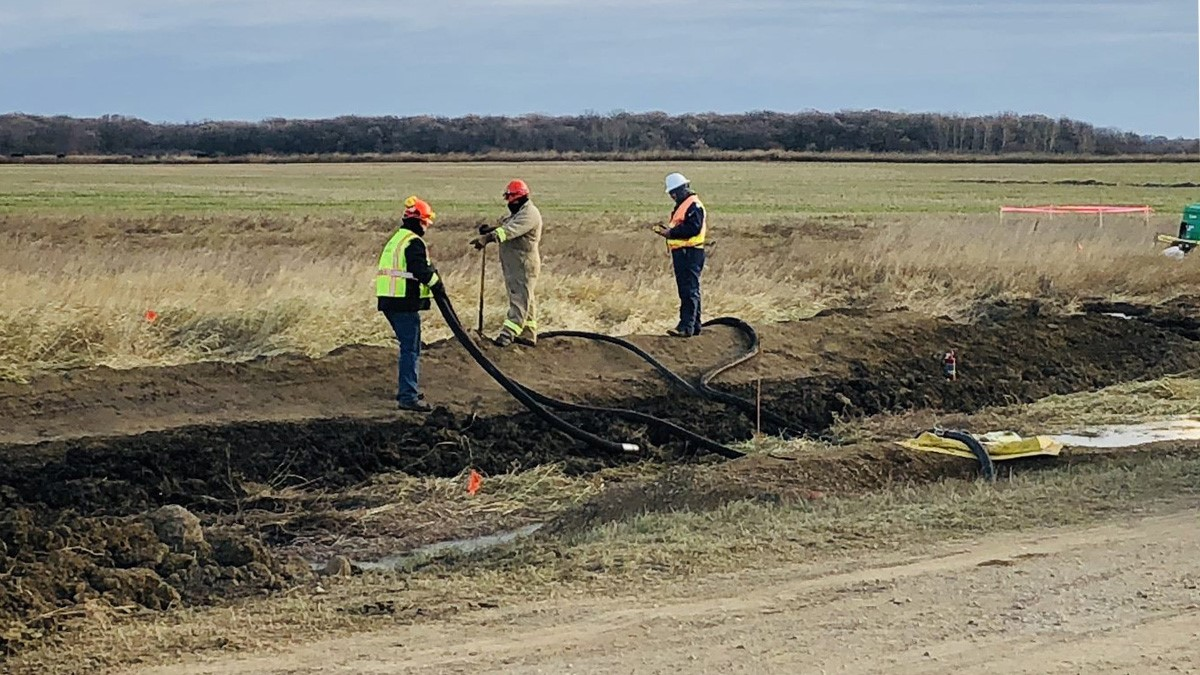 Workers survey the damage of a pipeline leak in a field near Edinburg, N.D. in this undated handout photo.