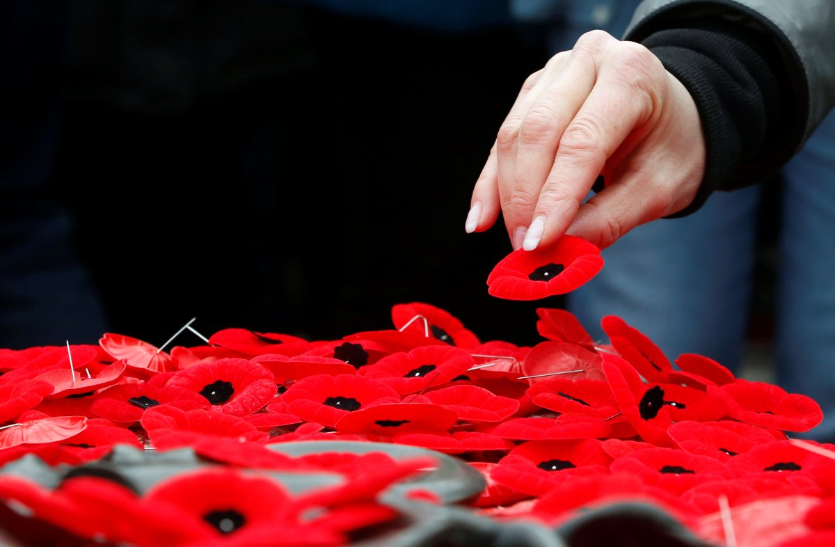 A woman places a poppy on the Tomb of the Unknown Soldier at the National War Memorial on Remembrance Day in Ottawa, Nov. 11, 2019.