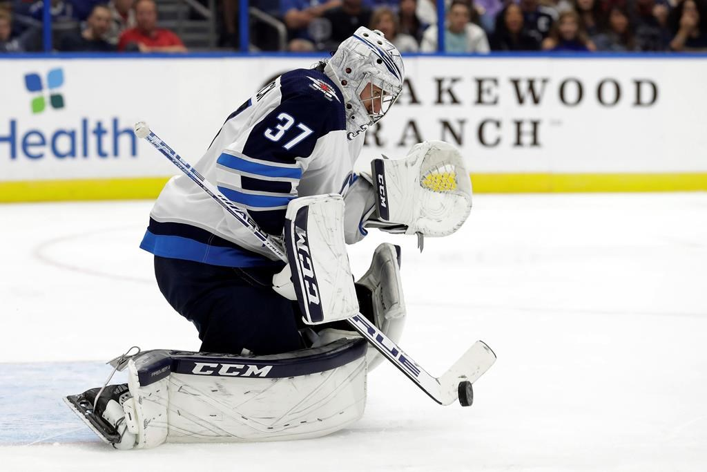 Winnipeg Jets goaltender Connor Hellebuyck (37) makes a save on a shot by the Tampa Bay Lightning during the second period of an NHL hockey game Saturday, Nov. 16, 2019, in Tampa, Fla. (AP Photo/Chris O'Meara).