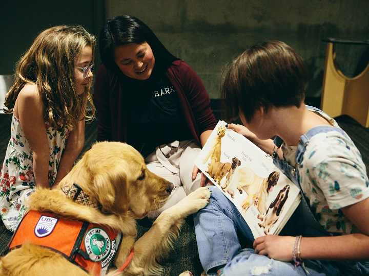 Golden retriever Abby listens while Annie Letheman, right, reads to her sister Ruby, with researcher Camille Rousseau, middle, observing.