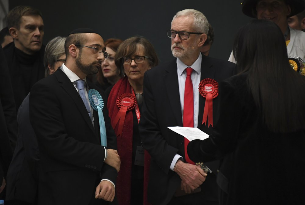 British opposition Labour Party leader Jeremy Corbyn, right, waits for the declaration of his seat in the 2019 general election in Islington, London, Friday, Dec. 13, 2019. The first handful of results to be declared in Britain's election are showing a surge in support for to the Conservatives in northern England seats where Labour has long been dominant.