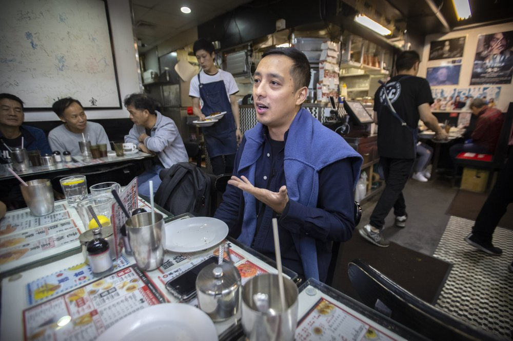 """In this Dec. 13, 2019, photo, Martin Khan of Capital Cafe talks about the effects on his business after he says his store was incorrectly labeled as an anti-protest """"blue"""" shop on online apps in Hong Kong. Protesters in Hong Kong are increasingly using their spending power to punish businesses they deem hostile to their cause. Apps are assigning color-coded labels to stores to help guide consumers. Protest-friendly stores are categorized as yellow. Blue is used to identify shops suspected of opposing protests. Protesters believe that by boycotting supposedly pro-establishment businesses, they can help shift the balance of power and wealth in the semi-autonomous Chinese territory."""