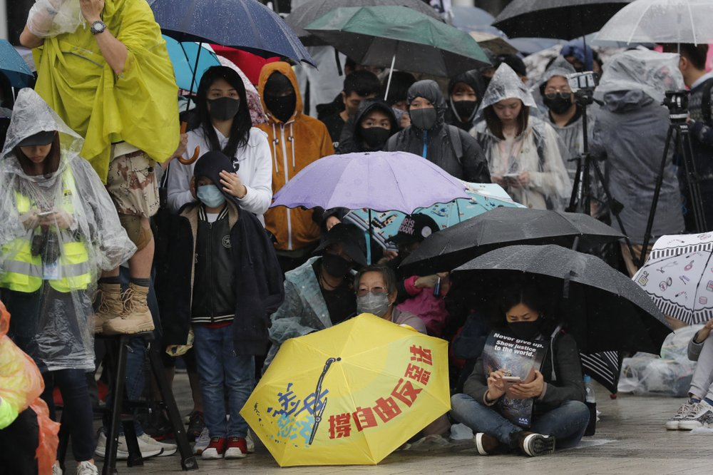 "Protesters sit down near an umbrella with the words ""Support freedom, Against Evil Law"" during a rally in Hong Kong on Sunday, Dec. 29, 2019. Protests that began in June over a proposed extradition law have spread to include demands for more democracy and other grievances."