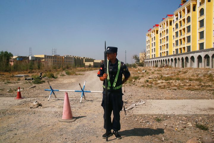 FILE PHOTO: A Chinese police officer takes his position by the road near what is officially called a vocational education centre in Yining in Xinjiang Uighur Autonomous Region, China September 4, 2018.