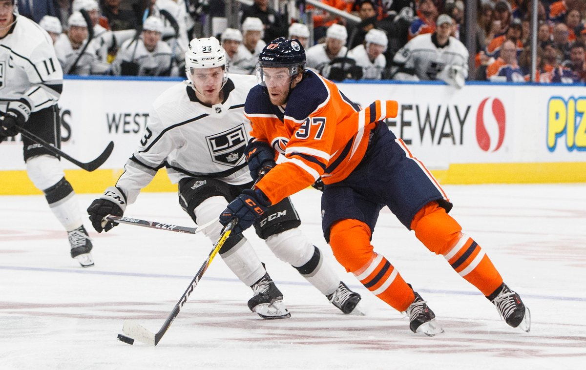 Los Angeles Kings' Tobias Bjornfot (33) chases Edmonton Oilers' Connor McDavid (97) during second period NHL action in Edmonton, Saturday, Oct. 5, 2019. THE CANADIAN PRESS/Jason Franson.