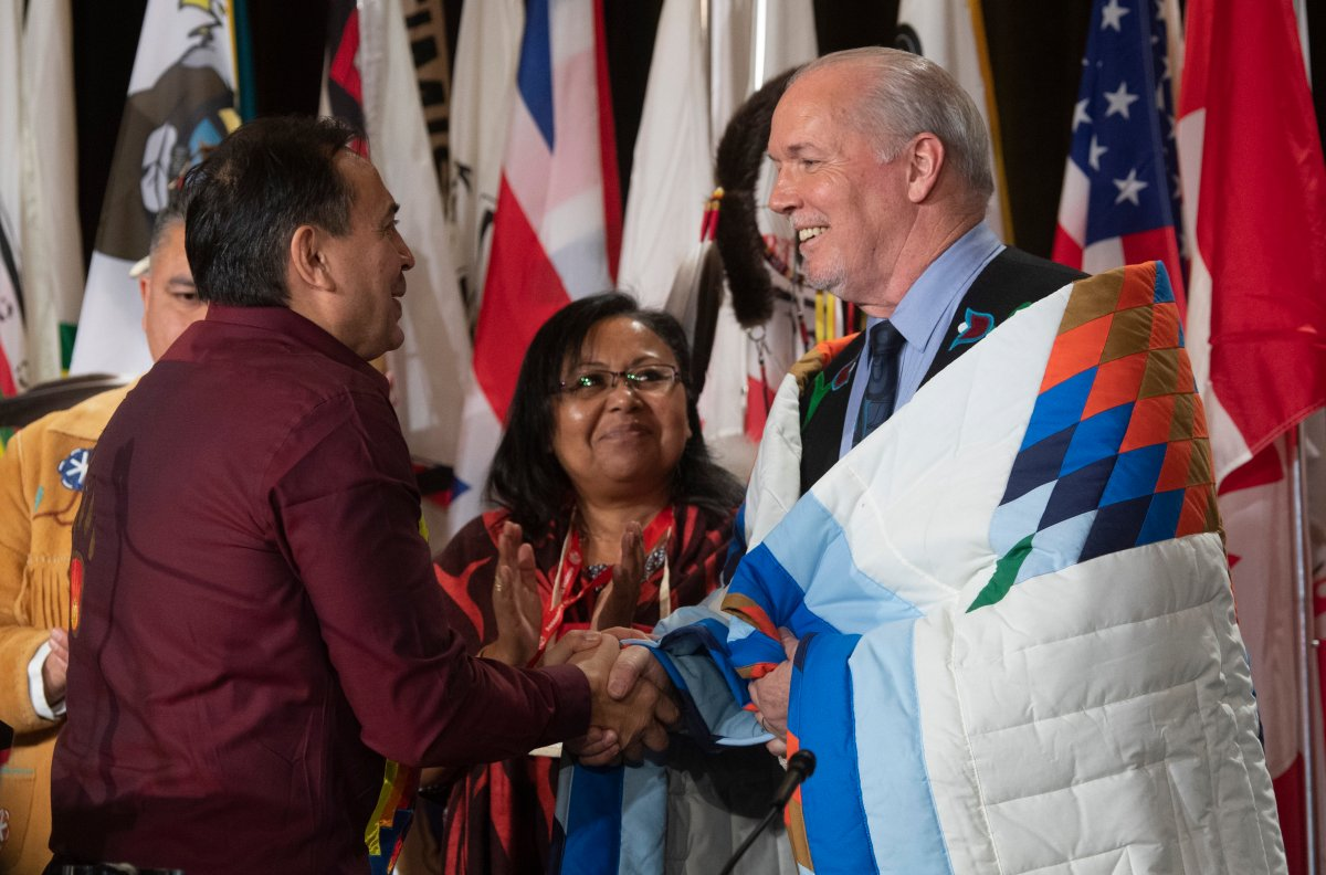 Assembly of First Nations Chief Perry Bellegarde speaks with B.C. Premier John Horgan after he was presented with a blanket during a ceremony at the Assembly of First Nations Special Chiefs Assembly in Ottawa, Tuesday, Dec. 3, 2019.