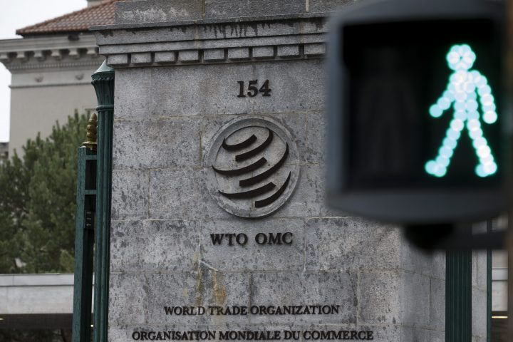 The WTO logo is pictured against a traffic light standing in front of the WTO headquarters in Geneva, Switzerland, 09 December 2019, during the opening of the World Trade Organization (WTO) General Council.