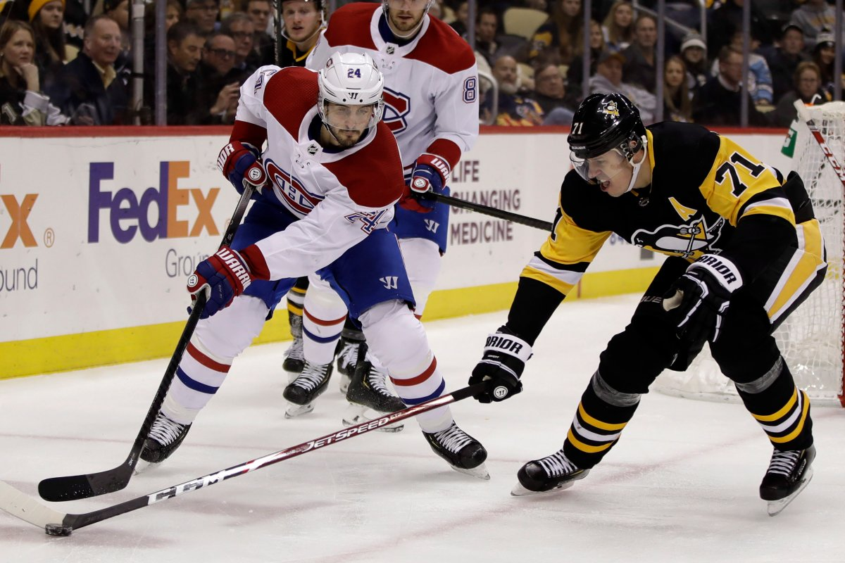Pittsburgh Penguins' Evgeni Malkin pokes the puck off the stick of Montreal Canadiens' Phillip Danault (24) during the second period of an NHL hockey game in Pittsburgh, Tuesday, Dec. 10, 2019.