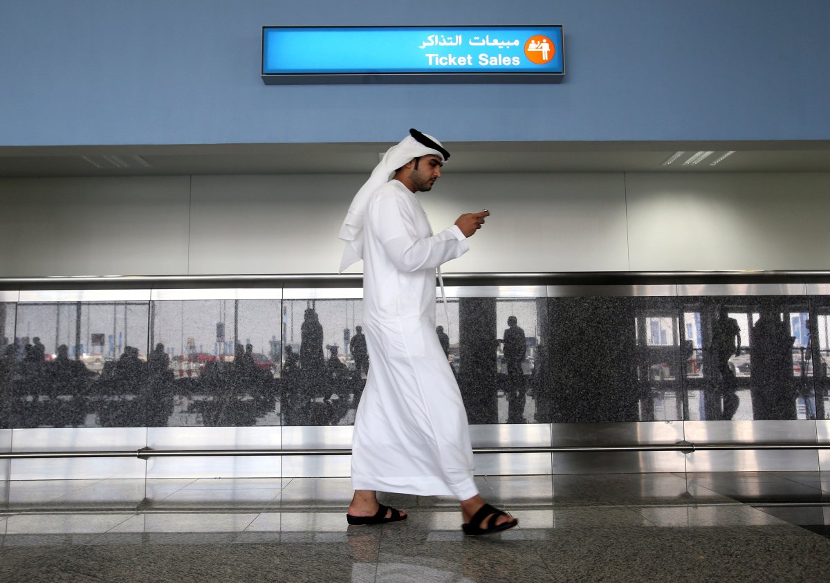 In this Oct. 27, 2013 file photo, a worker looks at his mobile phone at the newly opened Al Maktoum International Airport in Dubai, United Arab Emirates.