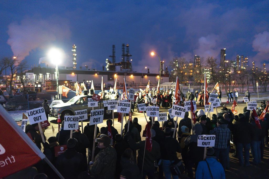 """Regina police have charged four men in relation to a """"confrontation"""" near the Co-op refinery Thursday. Pictured are members of Unifor Local 594 holding signs during a rally outside the Co-op Refinery on Dec. 5, 2019."""