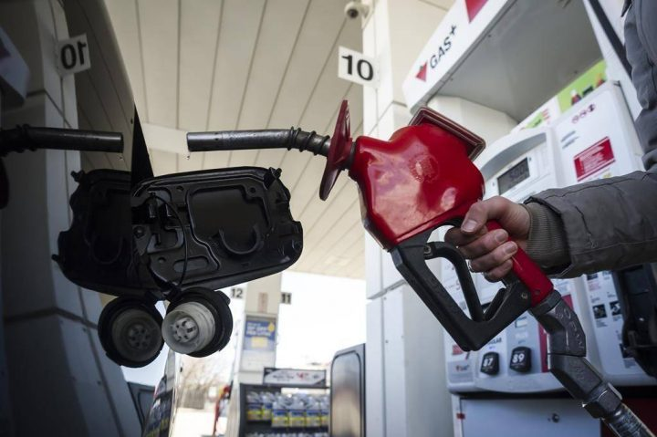 A woman fills up her car with gas in Toronto, on Monday, April 1, 2019.