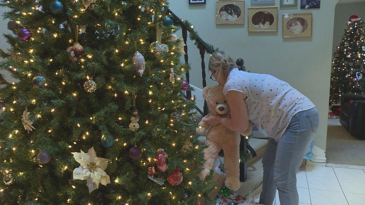 Alana Edwards places a gift for a senior near her home Christmas tree, Dec 14, 2019.