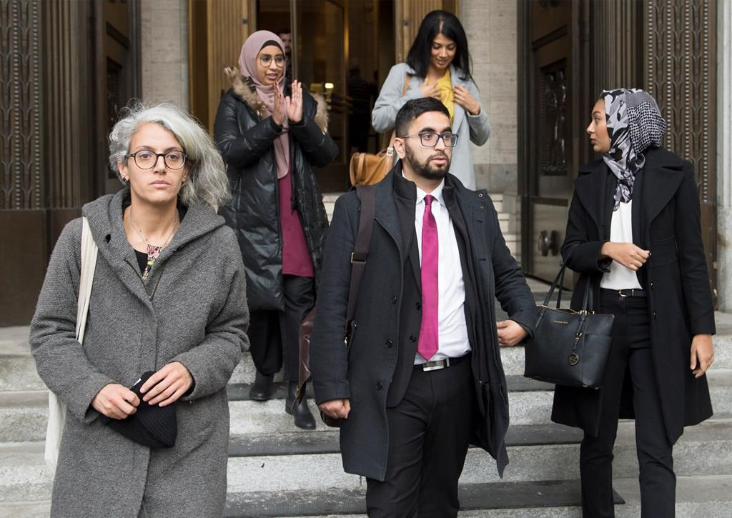 Members of the National Council of Muslims Mustafa Farooq, centre, and Bochra Manai, left, alongside supporters leave the Quebec Court of Appeal in Montreal, Tuesday, Nov. 26, 2019, where they are challenging Quebec's Bill 21.