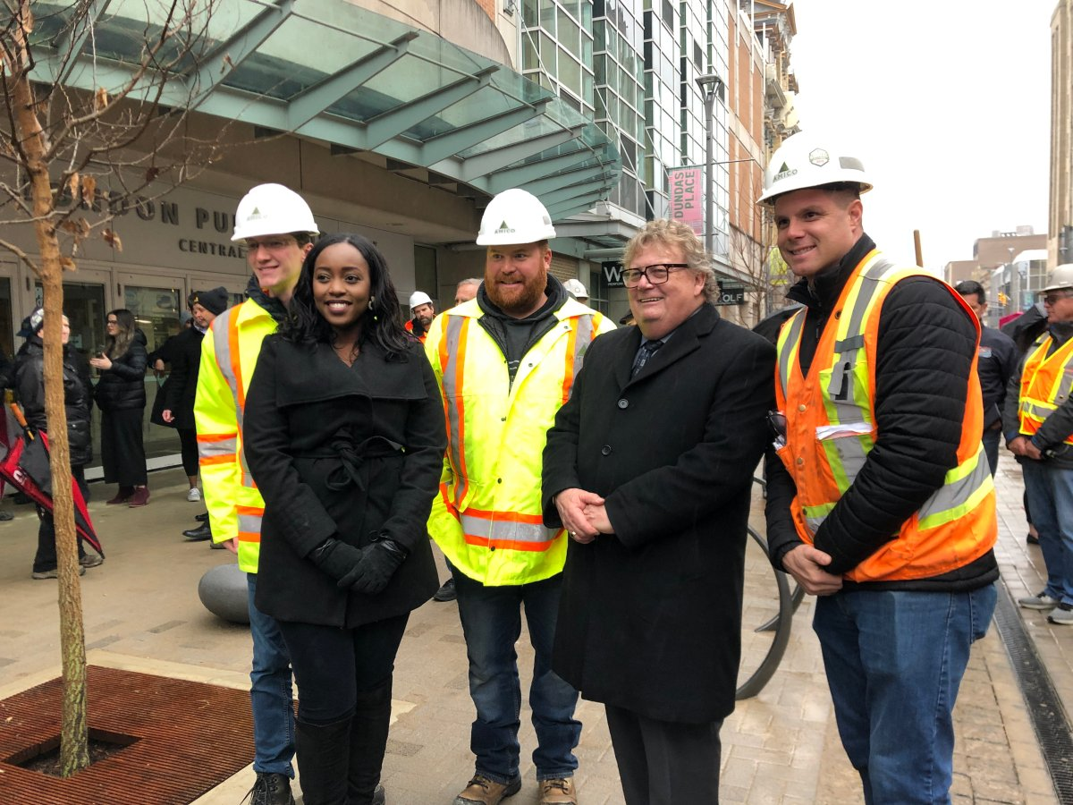 Councillor Arielle Kayabaga and Mayor Ed Holder with constriction workers at bricklaying ceremony on Dundas Place.