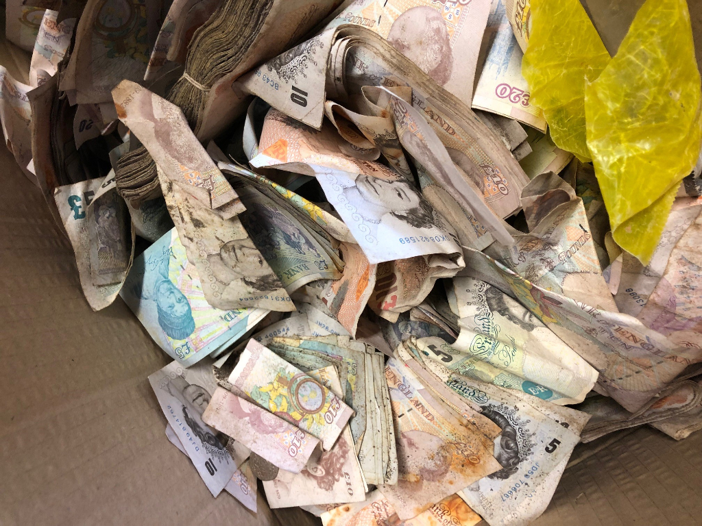 Scrap metal workers cut open an old safe and found thousands of dollars in cash inside.