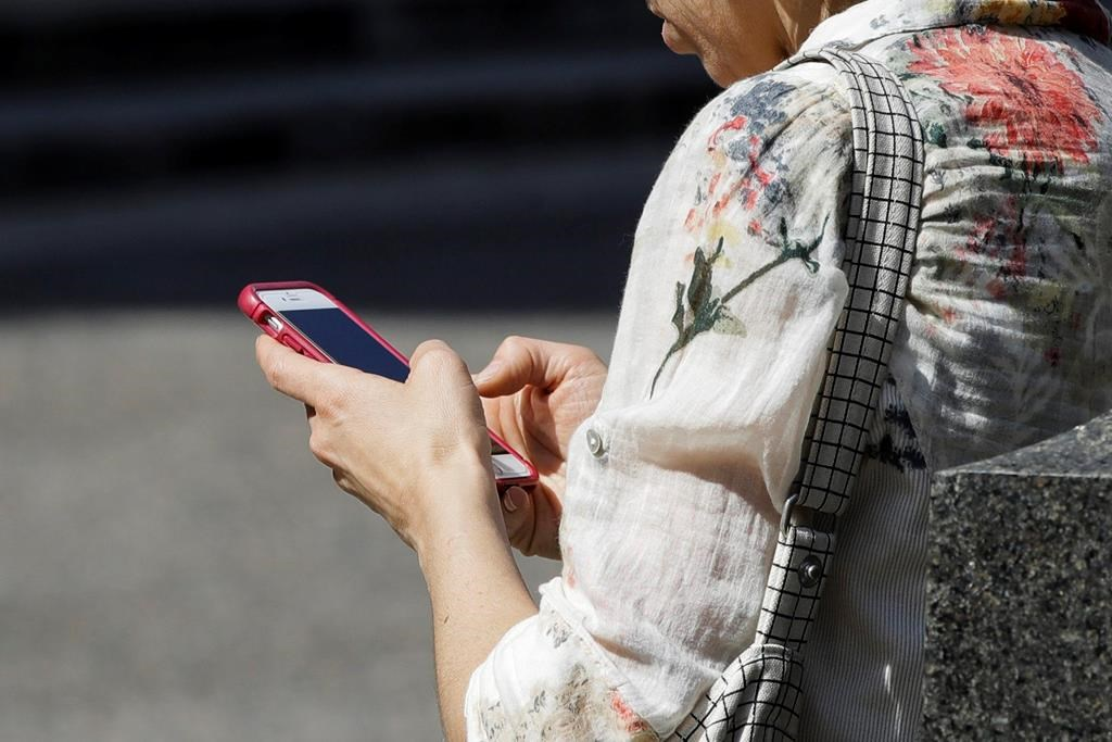 FILE - In this April 8, 2019, file photo, a woman browses her smartphone in Philadelphia. (AP Photo/Matt Rourke, File).