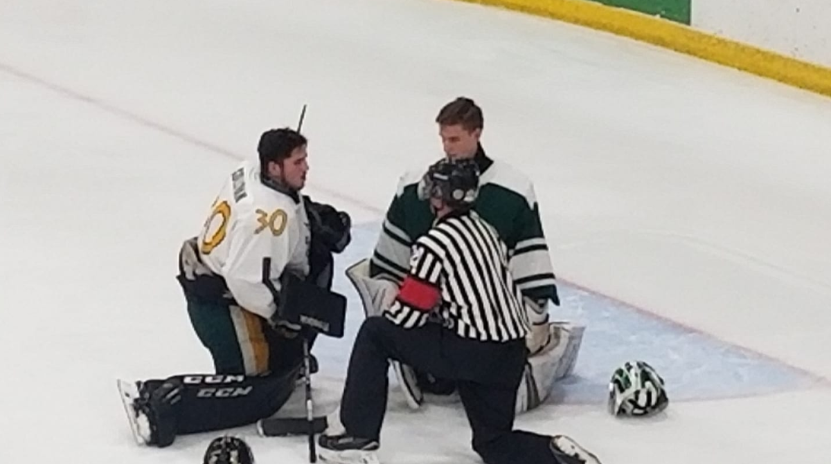 Goaltender T.J. Sullivan, left, offers tips to opposing goalie Davan Cloney during the first intermission of Saturday's high school boys hockey game.
