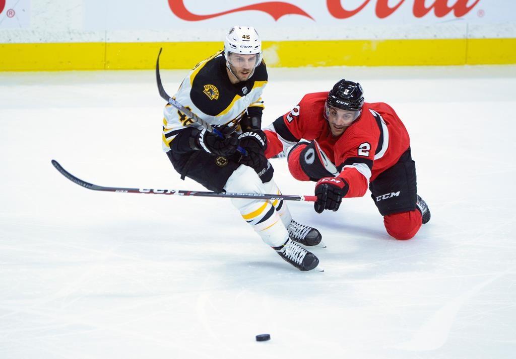 The Ottawa Senators' Dylan DeMelo dives for the puck around the Boston Bruins' David Krejci during third-period NHL action in Ottawa, Monday, Dec. 9, 2019.