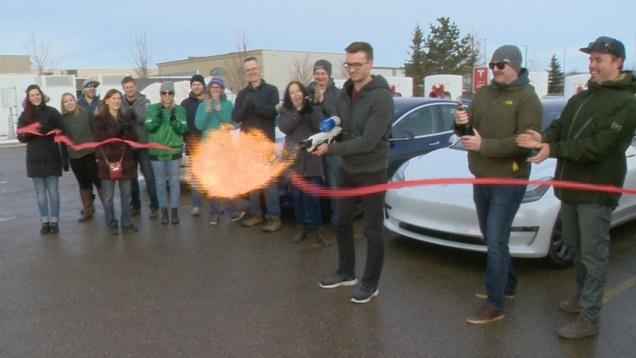 Tesla Owners of Saskatchewan melt the ribbon at Regina's first Supercharger station using an flamethrower designed by Elon Musk.