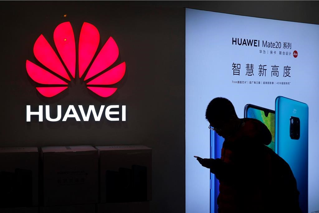 In this Dec. 11, 2018, photo, a man browses his smartphone outside a Huawei store at a shopping mall in Beijing. (AP Photo/Andy Wong).