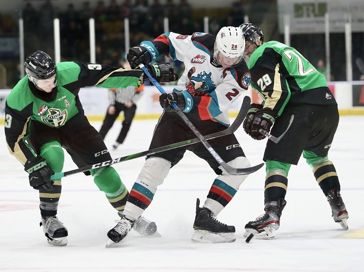 Nolan Foote of the Kelowna Rockets, middle, vies for the puck between Prince Albert defenceman Jeremy Masella, left, and left winger Justin Nachbaur, right, during WHL action on Friday, Dec. 6, 2019. The Saskatchewan government said the province's WHL teams and the SJHL need funding in order to survive the challenges they face due to the COVID-19 pandemic.