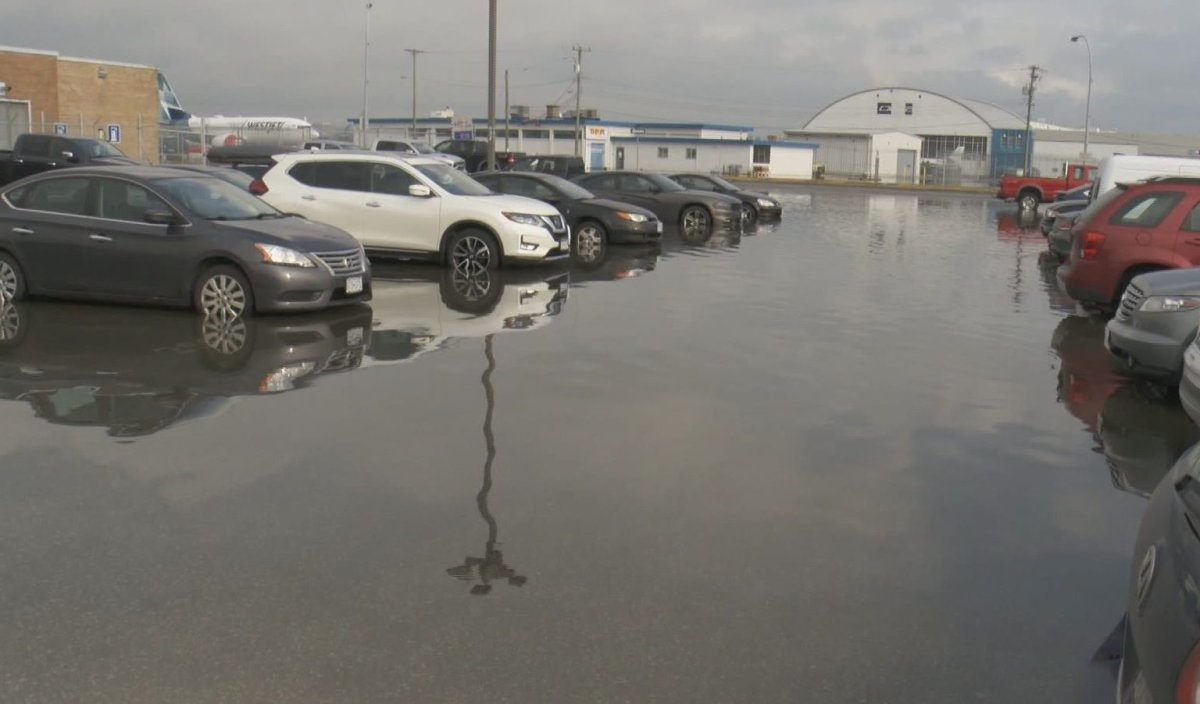 Parked cars sit in pooled water at Vancouver International Airport's south terminal on Dec. 14, 2019.