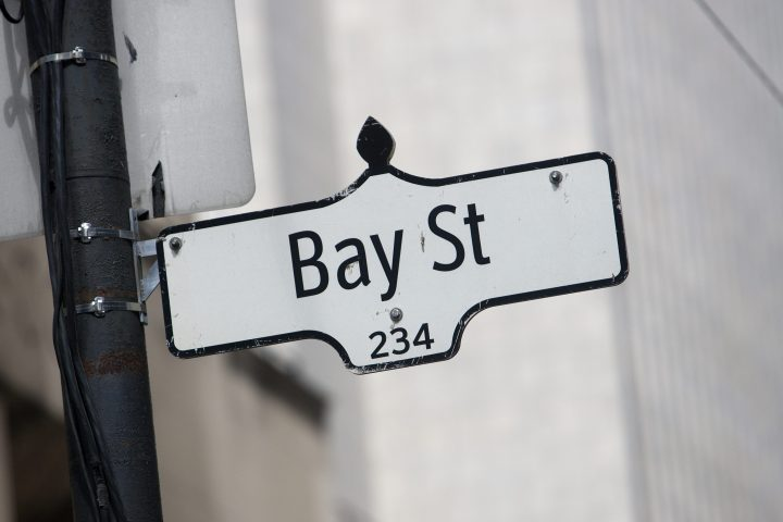 FILE: A Bay Street sign sits in downtown Toronto, Ontario on May 29, 2012. A new report says Canada's top CEOs have already earned as much as the average Canadian worker by 11:14 a.m. on Jan. 4.