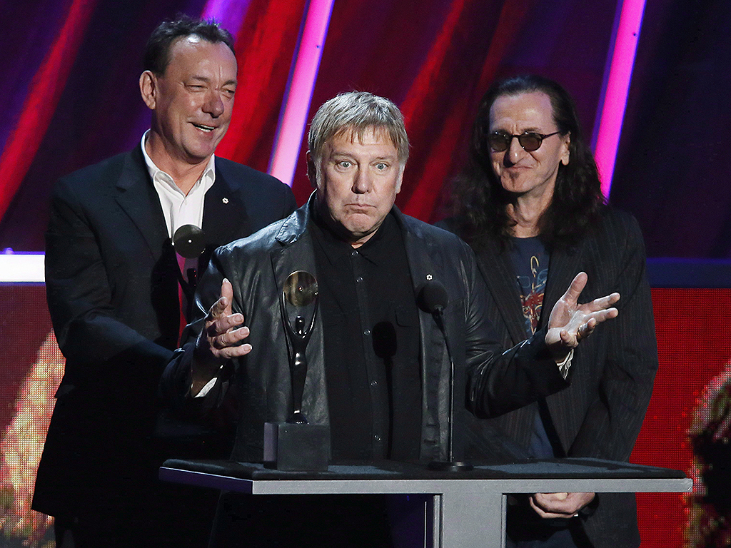 Alex Lifeson, centre, Neil Peart, left, and Geddy Lee, right, of Rush accept their band's induction into the Rock and Roll Hall of Fame at the Nokia Theatre on Thursday, April 18, 2013 in Los Angeles, Calif.