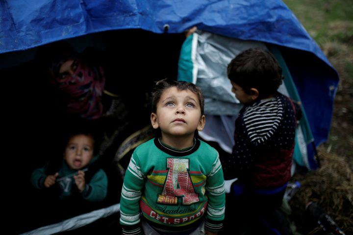 A Syrian refugee boy stands in front of his family tent at a makeshift camp for refugees and migrants next to the Moria camp on the island of Lesbos, Greece, Nov. 30, 2017.