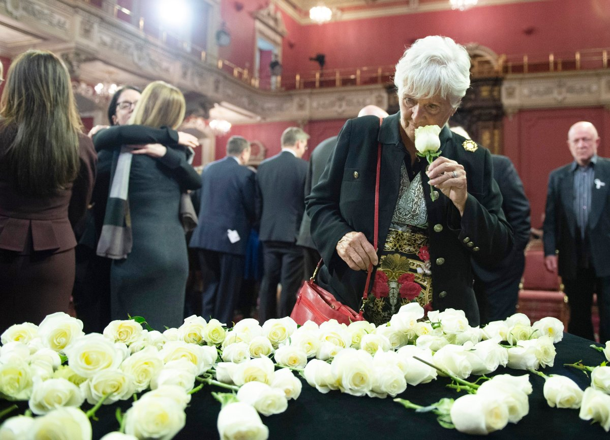 Suzanne Laplante Edward, mother of victim Anne-Marie Edward, smells a rose as she looks at the roses that were laid in commemoration during a ceremony marking the 30th anniversary of the Polythecnique shooting, Thursday, December 5, 2019.