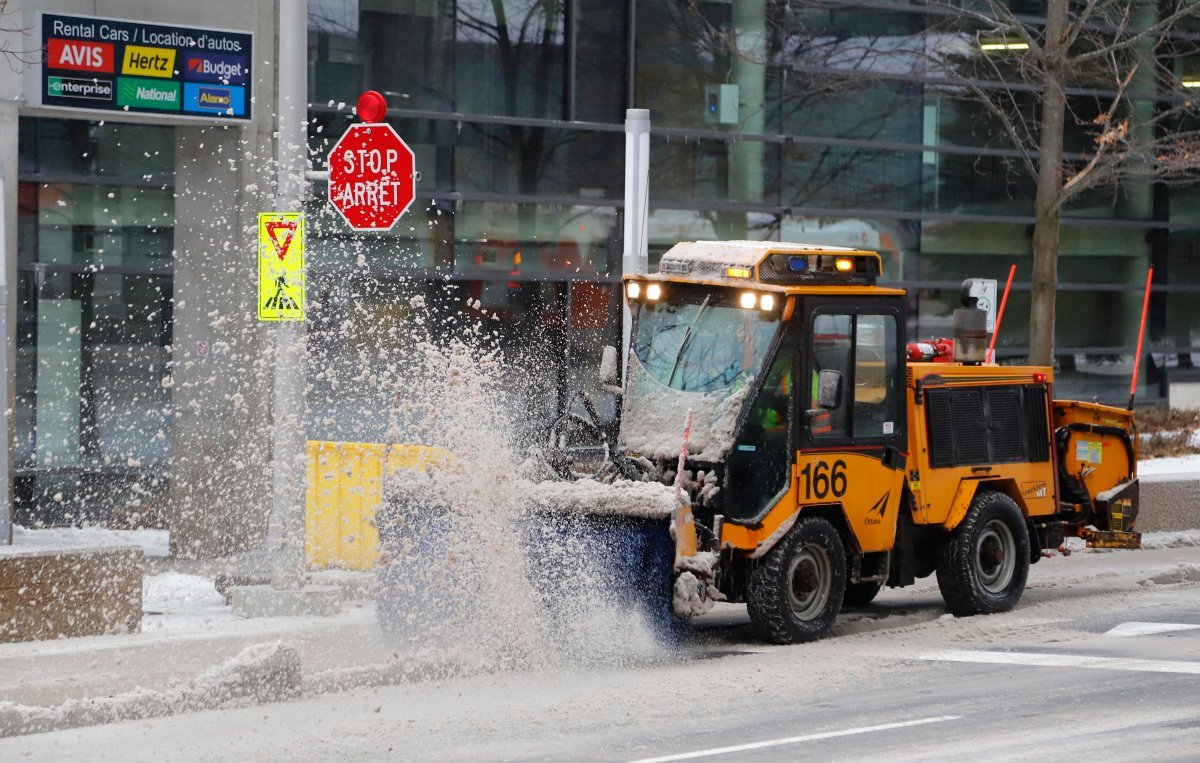 Workers clear ice and snow in front of Ottawa International Airport on Monday, Dec. 30, 2019.