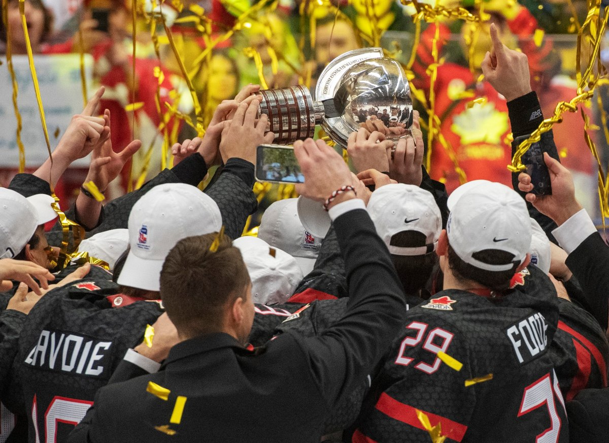 FILE -- Team Canada players reach for the trophy after defeating Russia 4-3 in the gold medal game at the World Junior Hockey Championships, Sunday, January 5, 2020 in Ostrava, Czech Republic.