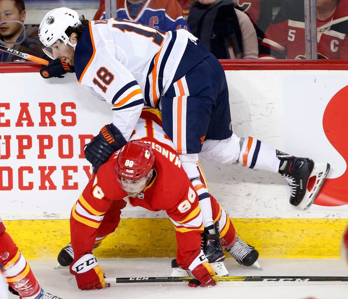 Edmonton Oilers' James Neal, top, knocks down Calgary Flames' Andrew Mangiapane during first period NHL hockey action in Calgary, Alta., Saturday, Jan. 11, 2020. THE CANADIAN PRESS/Larry MacDougal.