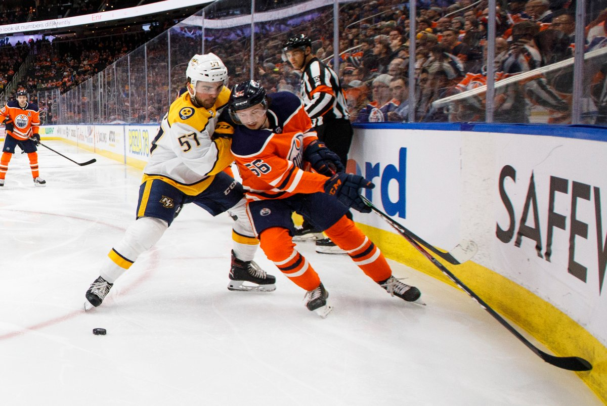 Nashville Predators' Dante Fabbro (57) and Edmonton Oilers' Kailer Yamamoto (56) battle for the puck during second period NHL action in Edmonton, Tuesday, Jan. 14, 2020. THE CANADIAN PRESS/Jason Franson.