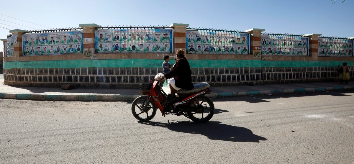 A motorcyclist drives past a wall with banners depicting portraits of late Houthi fighters allegedly killed in Yemen's ongoing conflict, in Sanaa, Yemen, 18 January 2020.