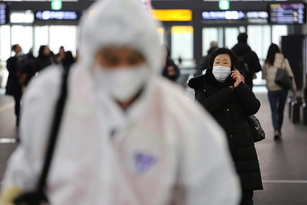 A woman wears a mask as an employee works to prevent a new coronavirus at Suseo Station in Seoul, South Korea, Friday, Jan. 24, 2020.