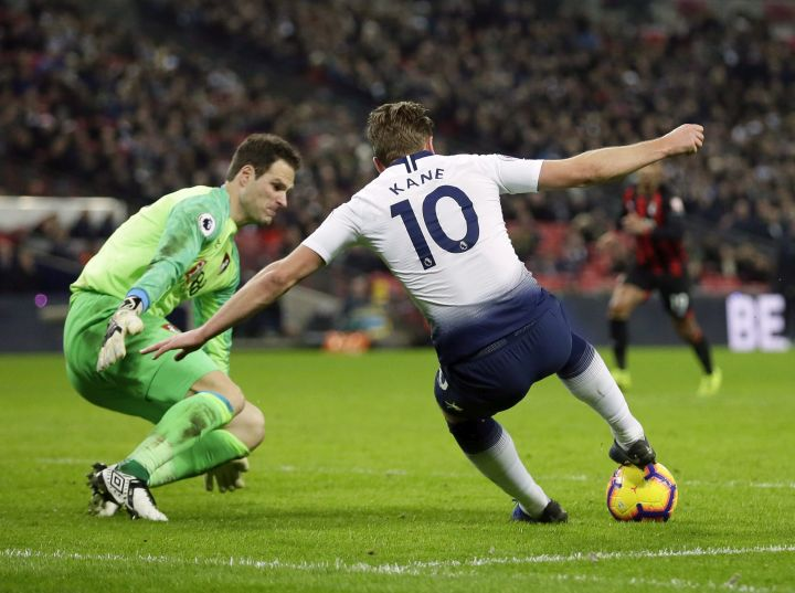 Bournemouth goalkeeper Asmir Begovic, left, makes a save in front of Tottenham's Harry Kane during the English Premier League soccer match between Tottenham Hotspur and Bournemouth at Wembley stadium in London, Wednesday, Dec. 26, 2018. Former Canadian under-20 goalkeeper Begovic has joined AC Milan on loan from England's Bournemouth through the end of June.