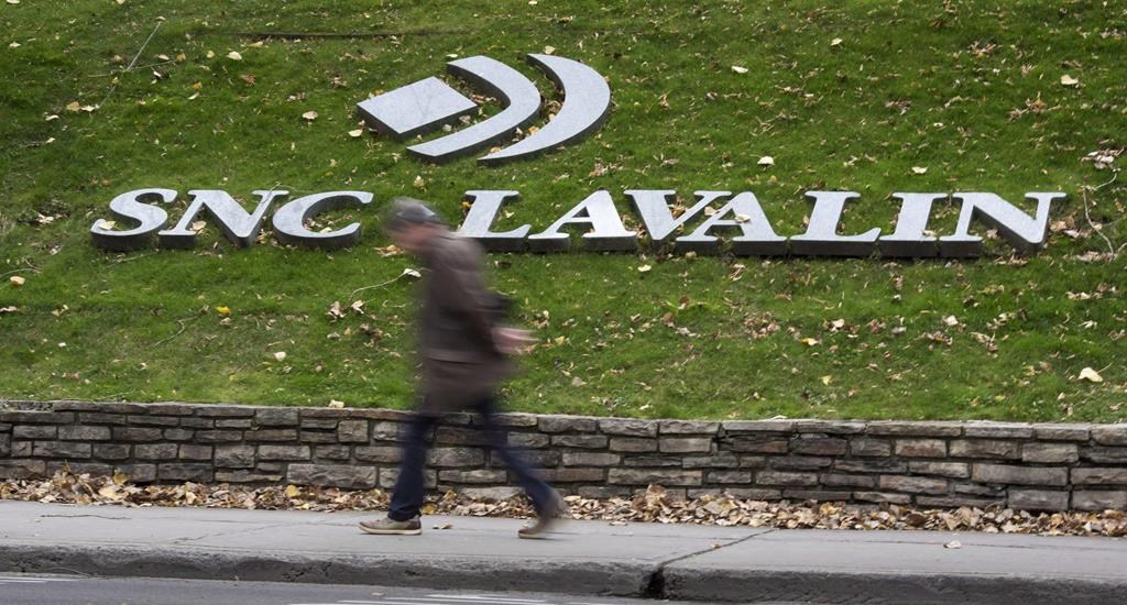 A man walks past the headquarters of SNC-Lavalin in Montreal on November 6, 2014.
