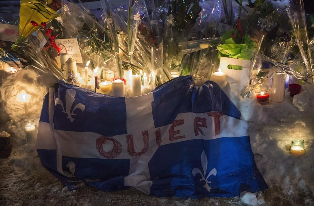 A Quebec flag with the word 'Open' written on it is shown in remembrance of six victims of a shooting at mosque during a vigil in Quebec City on Jan. 30, 2017.
