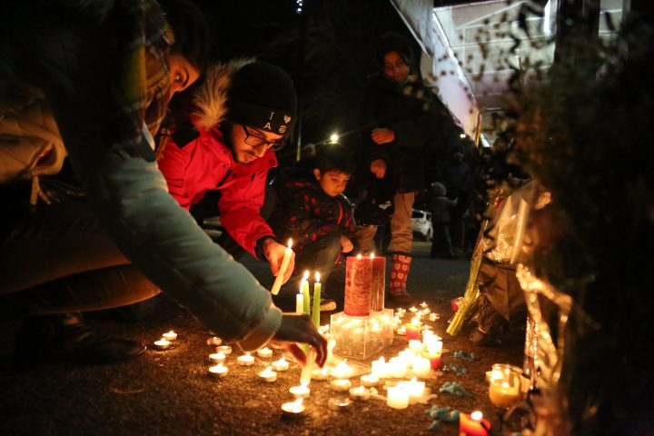 Mourners light candles and place flowers as they attend a vigil for the victims of a plane crash in Iran, outside Amir Bakery on Lonsdale ave. in North Vancouver, B.C., Canada on Jan. 8, 2020.