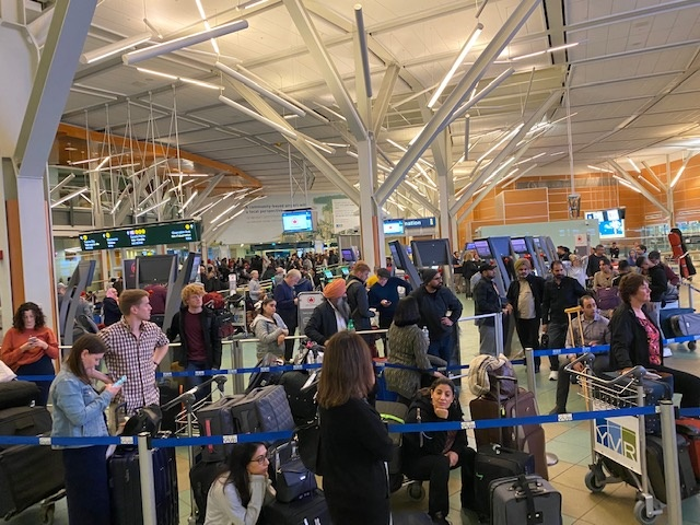 Frustrated passengers at YVR airport, their flights delayed due to a system failure with Air Canada's check-in system, requiring staff to manually create boarding passes.