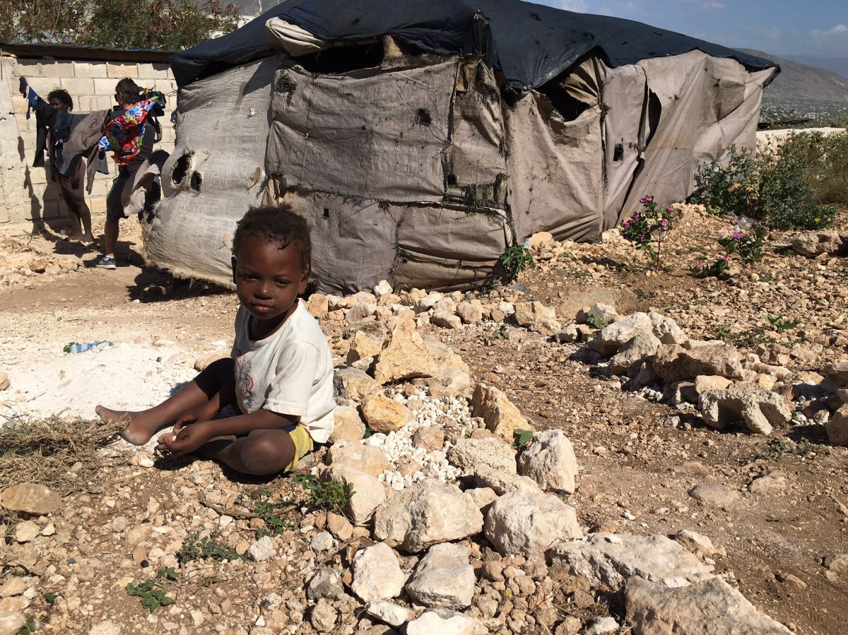 A small boy sits outside the tent he lives in with his family in Canaan, Haiti, January 2020. (Valerie Laillet)